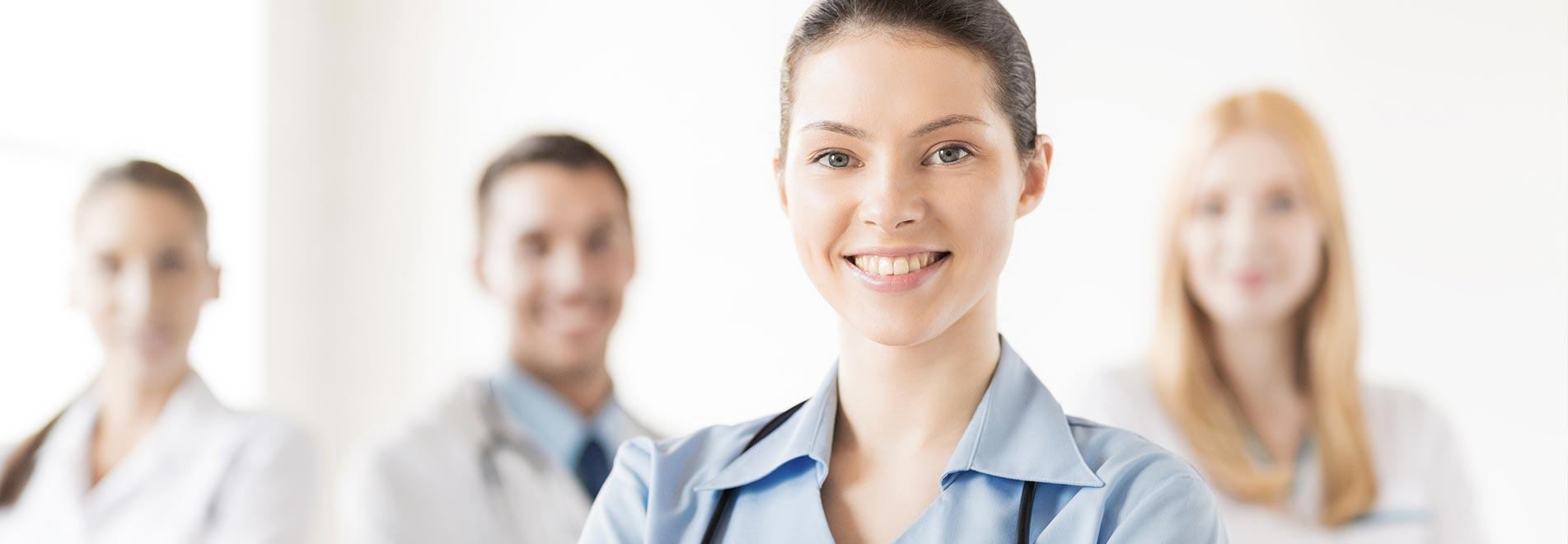 Zahntechnikerin und drei Zahnärzte in Hintergrund