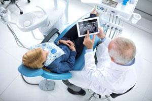 Zahnarzt an Behandlungsstuhl schaut auf Tablet mit Roentgenbild