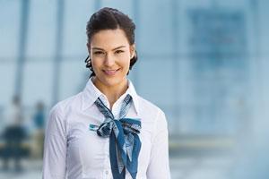 Weiblicher Zahntechniker mit weisser Bluse lächelt in Kamera vor blauem Hintergrund